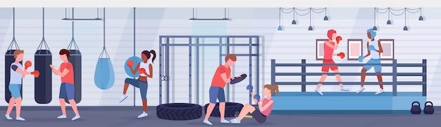 Mescolare i pugili di razza praticando esercizi di boxe combattenti in guanti che esercitano sul ring arena fight club con sacchi da boxe moderna palestra interni stile di vita sano concetto orizzontale