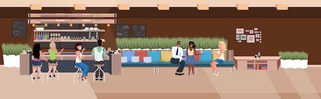 Mescolare la razza persone che bevono bevande amici seduti ai tavolini dei caffè visitatori che trascorrono del tempo insieme moderno ristorante interno piatto orizzontale a figura intera
