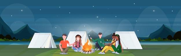 Mix corsa escursionisti gruppo torrefazione caramelle marshmallow sul fuoco escursionismo campeggio concetto viaggiatori sull'escursione campeggio notte montagne paesaggio natura sfondo orizzontale a figura intera