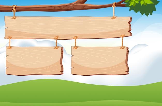 Modello di cartello in legno sul ramo con sfondo di cielo