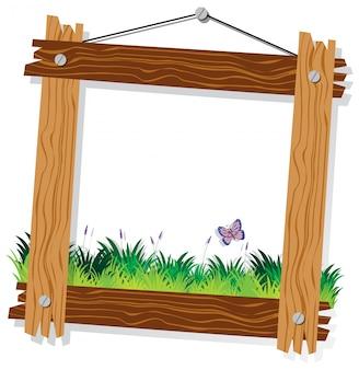 Modello di cornice in legno con erba verde e farfalla