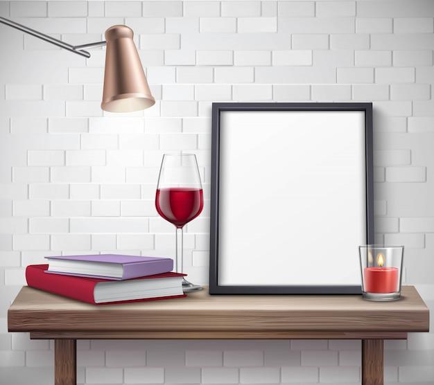 Modello di cornice realistica sul tavolo con bicchiere di vino candela lampada e libri
