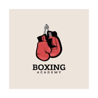 Modello di logotipo di boxe con guantoni da boxe appesi.