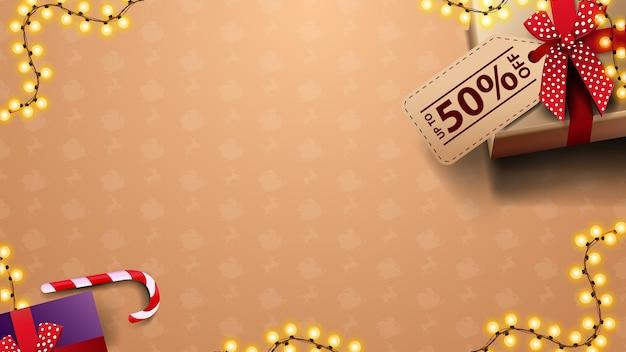 Modello di natale per le tue arti con regali con cartellino del prezzo e ghirlanda, vista dall'alto