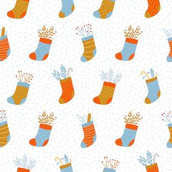 Modello di vacanza senza soluzione di continuità con diversi calzini di natale, caramelle e ramoscelli.