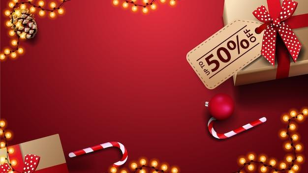 Modello rosso per l'insegna di sconto con il fondo del copyspace, il contenitore di regalo, le palle di natale e il bastoncino di zucchero, vista superiore