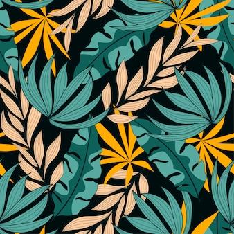 Modello senza cuciture astratto con piante e foglie colorate tropicali su sfondo nero