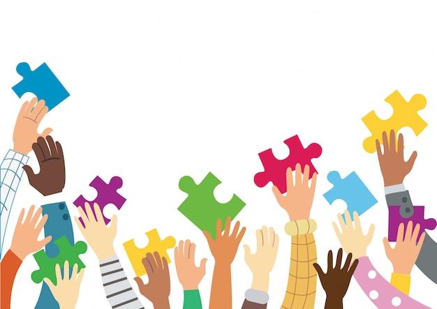Molte mani che tengono i pezzi del puzzle colorato
