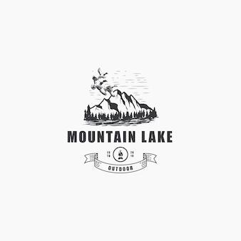 Montagna all'aperto con pini e logo di anatre volanti