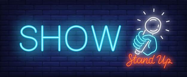 Mostra l'insegna al neon. glowing stand up testo e mano con microfono