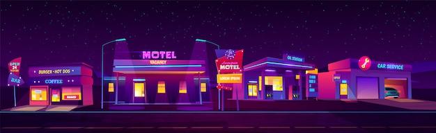 Motel lungo la strada di notte con parcheggio, stazione dell'olio, hamburger e bar e servizio auto incandescente