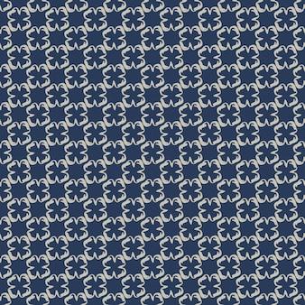 Motivo geometrico con piccoli elementi bianchi su sfondo blu scuro.