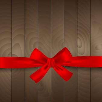 Nastro rosso di natale su fondo di legno