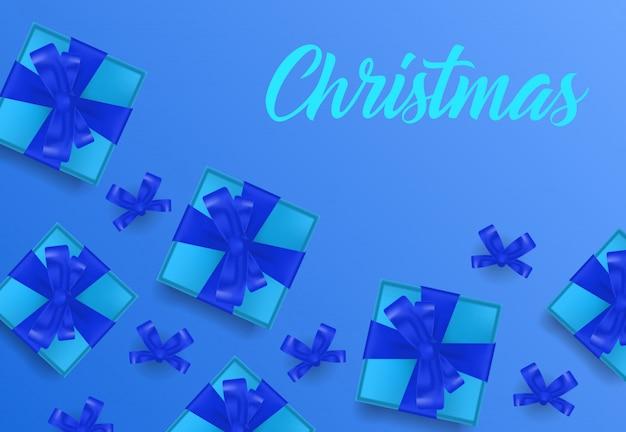Natale scritte su sfondo blu con scatole regalo