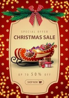 Offerta speciale, saldi natalizi, banner con ghirlanda, trama a pois rossa e slitta di babbo natale con regali