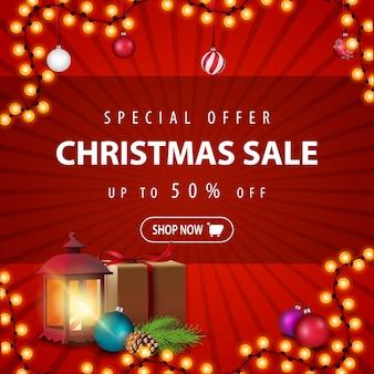 Offerta speciale, saldi natalizi, fino al 50% di sconto, banner sconto rosso con regalo, lanterna vintage, ramo di un albero di natale con un cono e una palla di natale