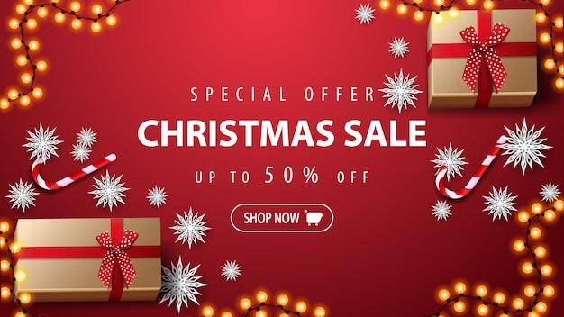 Offerta speciale, saldi natalizi, fino al 50% di sconto. insegna rossa di sconto con i regali, la canna di candys, i fiocchi di neve di carta e la ghirlanda sulla tavola rossa, vista superiore.