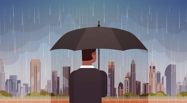 Ombrello della tenuta dell'uomo che esamina tempesta nel ciclone enorme del ciclone del fondo della pioggia della città nel concetto di disastro naturale della città