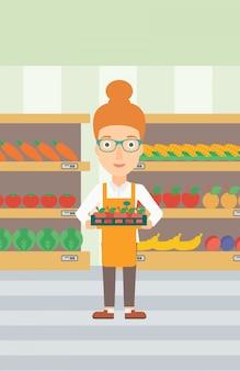 Operaio del supermercato con scatola piena di mele.