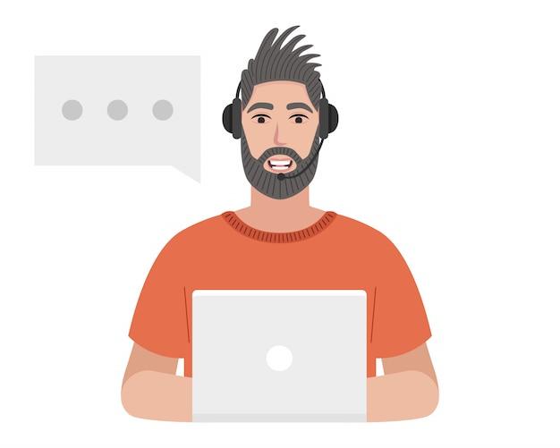 Operatore di call center con un auricolare sta scrivendo sul laptop. uomo barbuto che parla