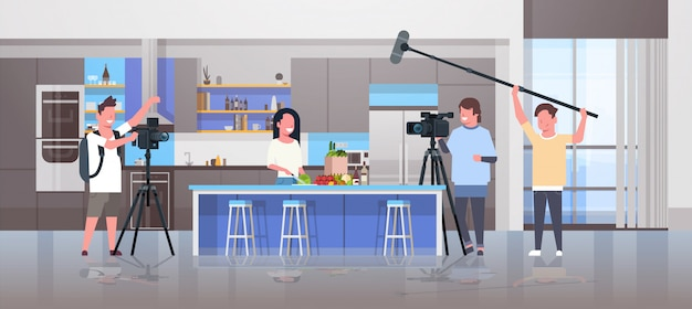 Operatori che utilizzano la videocamera per la registrazione di cibo blogger donna preparazione gustosi piatti videografi utilizzando attrezzature professionali cucina blog film produzione concetto cucina interno orizzontale