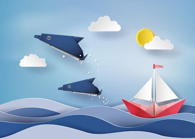 Origami fatto delfino e barca a vela galleggiante sul mare.