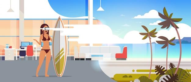 Orizzontale surfer piano di vacanze estive di concetto della cuffia avricolare di visione della cuffia avricolare della spiaggia della realtà virtuale dell'oceano della tavola di surf della tenuta di vetro di usura del surfista della donna