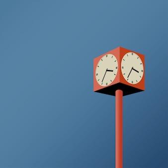 Orologio pubblico in tono arancione presso la stazione ferroviaria pubblica nel pomeriggio quando tramonta il sole