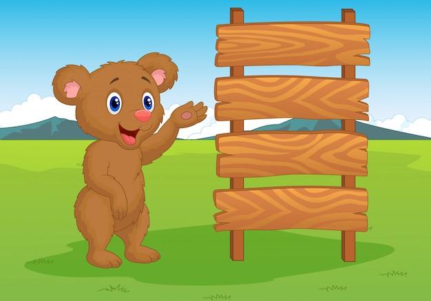 Orso di bambino dei cartoni animati con cartello in legno