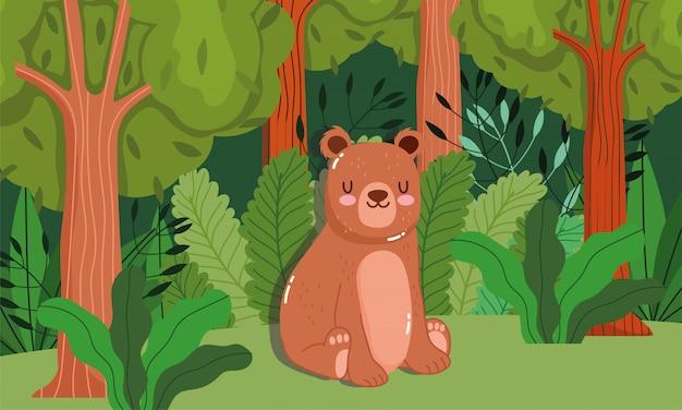 Orso sveglio che si siede sopra sulla foresta verde