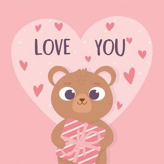 Orso sveglio del giorno di biglietti di s. valentino felice che tiene il cuore del contenitore di regalo romantico