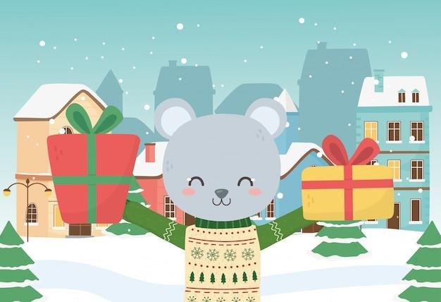 Orso sveglio di celebrazione di buon natale con la neve della città dei regali del maglione