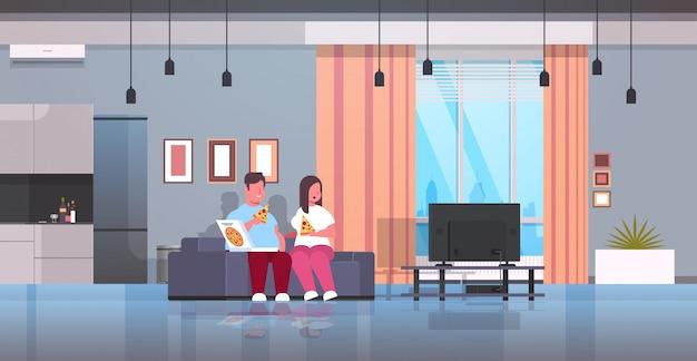Over size coppia mangiare pizza uomo donna a guardare la tv seduto sul divano malsano fast food obesità