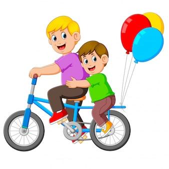 Padre con bambino felice in sella a una bicicletta