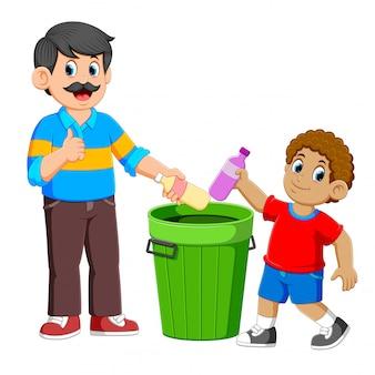 Padre e suo figlio che raccolgono la bottiglia di plastica della spazzatura