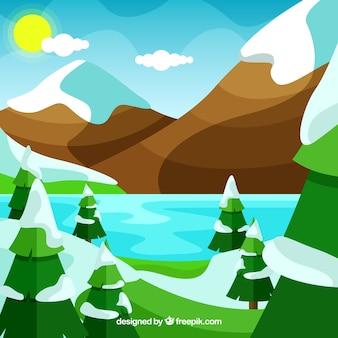 Paesaggio con montagne innevate e pini