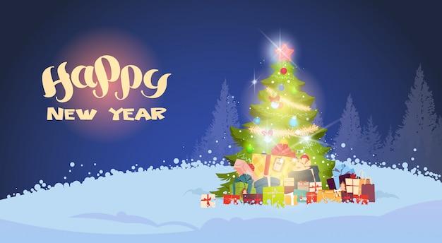 Paesaggio invernale bellissimo albero di natale che splende di notte su snowy forest holiday greeting card