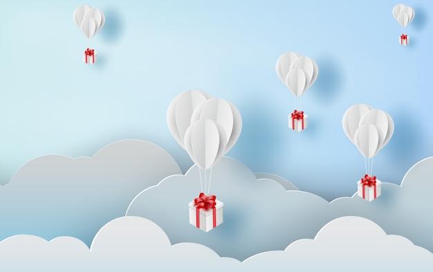 Palloncino bianco galleggiante e confezione regalo sul cielo blu dell'aria.