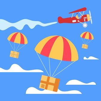 Paracadute con scatole che cadono dall'aeroplano