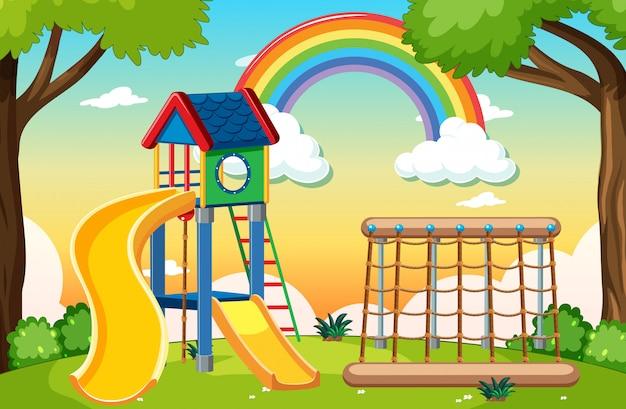 Parco giochi per bambini nel parco con arcobaleno nel cielo in stile cartoon di giorno