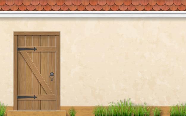 Parete dello stucco di una casa con una vecchia porta di legno