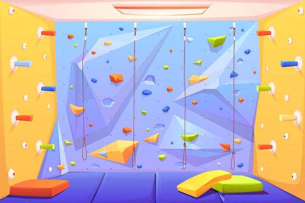 Parete per arrampicata su roccia con impugnature, stuoie e corde