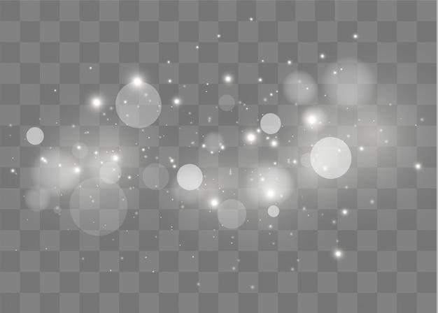 Particelle di polvere magica scintillante. le scintille bianche scintillano con uno speciale effetto di luce.