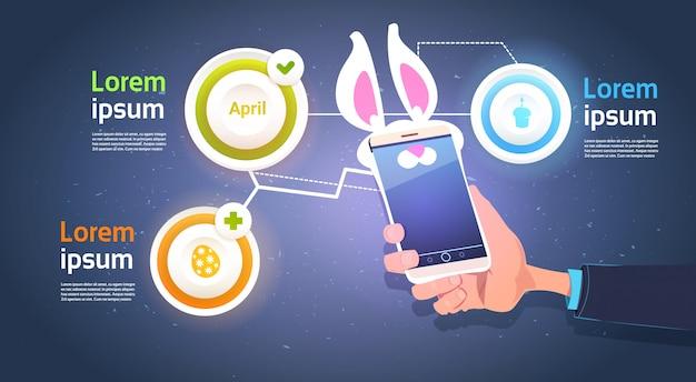 Passi lo smart phone della tenuta con le orecchie del coniglietto sopra gli elementi di infographic del modello per il fondo felice di festa di pasqua