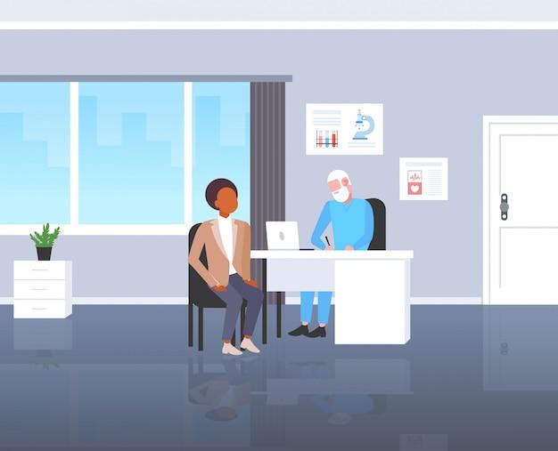 Paziente che riceve un uomo afroamericano di prescrizione che ha consultazione con il medico senior che si siede all'ufficio medico dell'ospedale moderno moderno di concetto di medicina e di sanità del posto di lavoro integrale