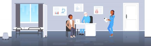 Paziente che riceve un uomo di prescrizione che ha consultazione con medico senior che si siede nell'orizzontale integrale interno dell'ufficio medico dell'ospedale moderno moderno di concetto di sanità della medicina del posto di lavoro