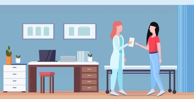 Paziente che riceve una prescrizione dalla donna del terapista che ha consultazione con la medicina del medico femminile e orizzontale orizzontale integrale interno dell'ufficio moderno di concetto di sanità