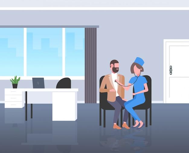 Paziente femminile dell'uomo d'affari d'esame di medico dallo stetoscopio che controlla integrale interno moderno della stanza di ospedale di concetto di sanità della medicina del respiro o del battito cardiaco