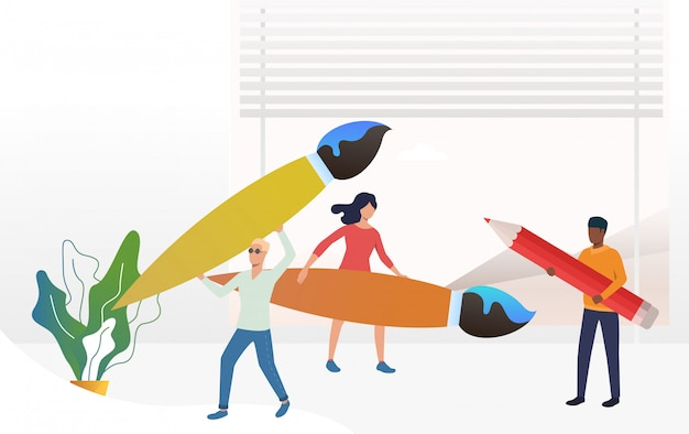 Persone in piedi e in possesso di grandi pennelli e matita