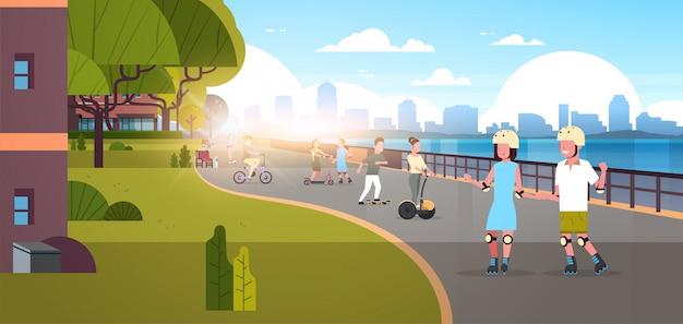 Persone in sella a biciclette e pattini nel parco